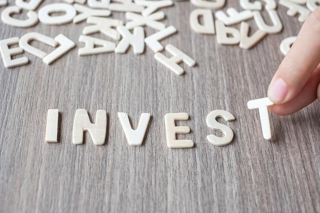 Investeer woord van houten alfabetbrieven. bedrijf en idee concept