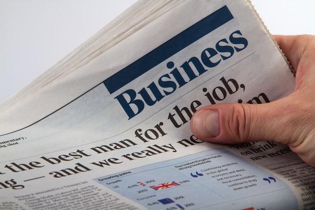 Investeerder die de nieuwste krant van het bedrijf houdt en leest.