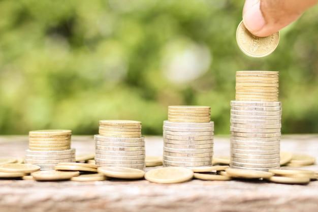 Investeerder hand vasthouden en neerzetten van een gouden munt met spaargeld op foto wazige achtergrond bedrijfsinvesteringen en geld besparen concept