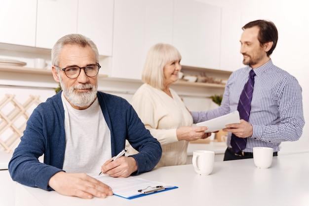 Investering van toekomstige eigenaren. nadenkende bebaarde senior man zit en ondertekent contract huis investeringen terwijl zijn vrouw de notaris begroet