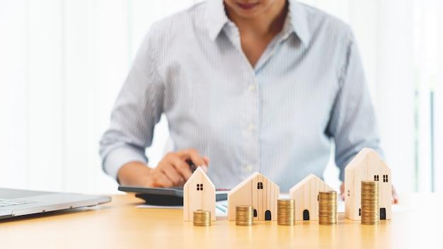 Investeringen in onroerend goed en hypotheek financieel concept, hand van een zakenman die munten stapelt voor investeringen in onroerend goed, sparen voor kopen voor huisvesting of speculatie.
