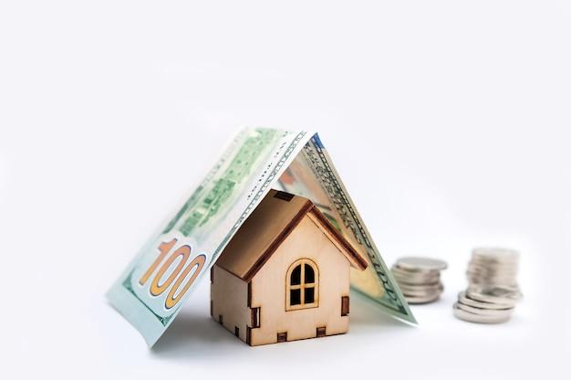 Investeringen onroerend goed concept. hypotheekconcept voor geldhuis dat van muntstukken wordt gemaakt. huis modelgeld