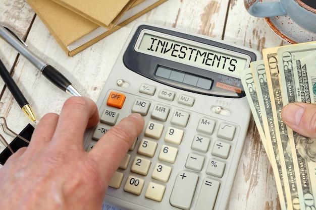 Investeringen woord op rekenmachine. bedrijfs- en belastingconcept.