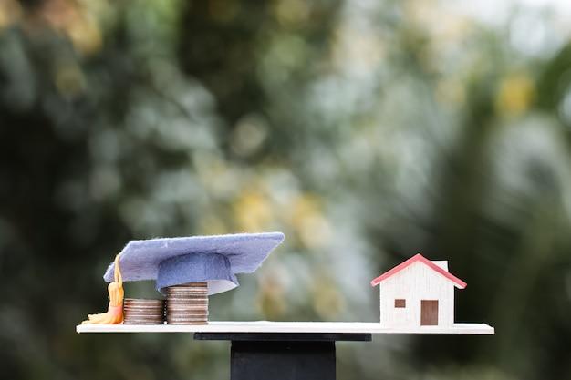 Investerings- en onderwijsbesparende ideeën: dropshipping geldmunten naar afstuderen cap op houtbalans met huismodel. concept van educate university vereist geldbesparing, zal naar huis graad brengen.