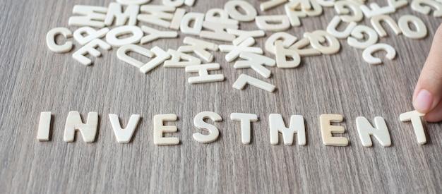 Investeringswoord van houten alfabetbrieven. bedrijf en idee concept