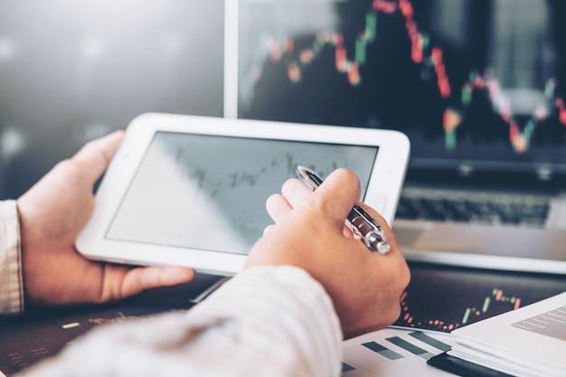 Investment stock market entrepreneur business man met behulp van tablet bespreken en analyse
