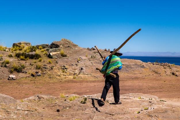 Inwoner van het eiland taquile met een geweven tas en boomstammen
