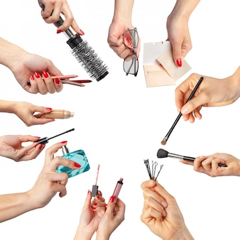 Inzameling die van handen hulpmiddelen voor make-up houdt op wit wordt geïsoleerd