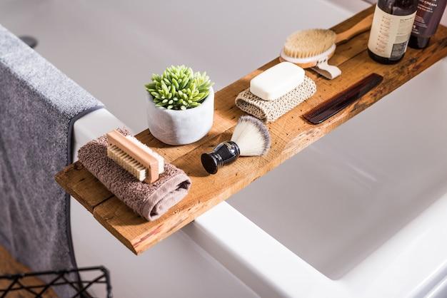 Inzameling van badkamermateriaal handdoeken, scheerkwast, haarborstel, shampoos en zeep op een hout