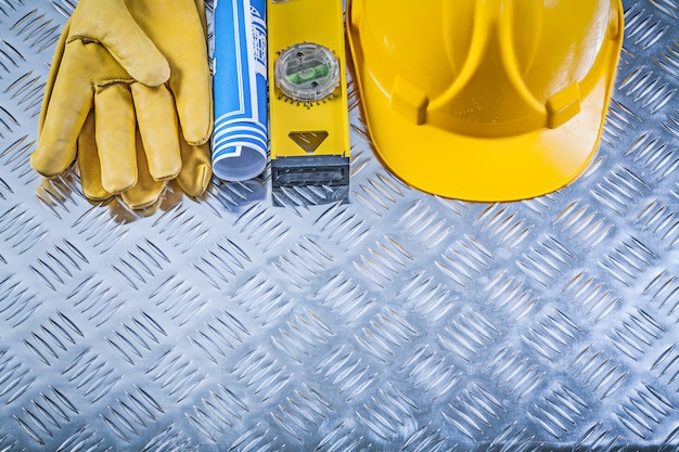 Inzameling van blauwe gerolde blauwdrukken die het niveau van de de handschoenenbouw van de helmveiligheid bouwen op golf metaalachtergrond