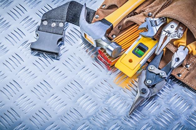 Inzameling van bouw het bewerken in hulpmiddelriem op golfmetaal achtergrondonderhoudsconcept