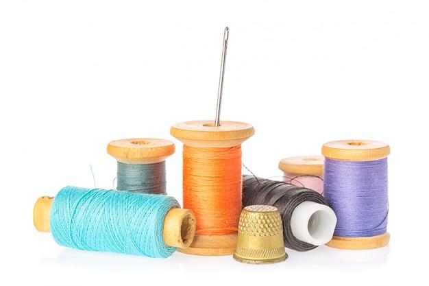 Inzameling van de spoelen van de kleurendraad met naald en vingerhoedje dat op witte achtergrond wordt geïsoleerd.