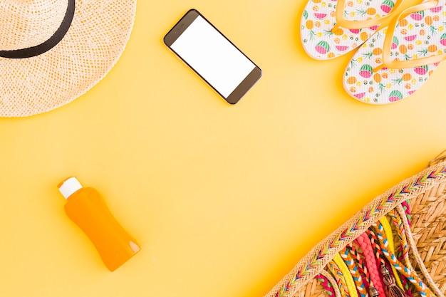 Inzameling van de tropische bezittingen en telefoon van de strandvakantie op gele achtergrond