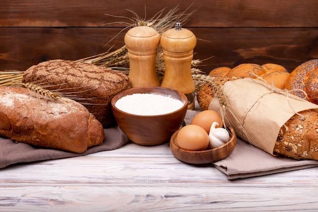 Inzameling van graanbrood en gebakken goederen op houten oppervlakte. diverse broodjes. gezond broodassortiment. winkelen voedsel supermarkt concept. brood gemaakt van tarwe- en roggemeel. bakkerijproducten