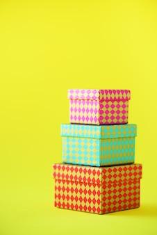 Inzameling van kleurrijke giftdozen op gele achtergrond. cadeaus voor verjaardag en feest. kerstmis, nieuw jaarconcept