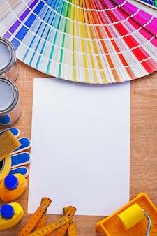 Inzameling van verfhulpmiddelen en kleurenpaletgids op blad van document bouwconcept