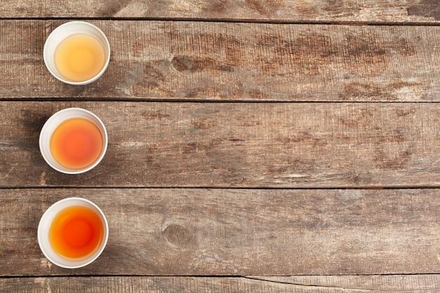 Inzameling van verschillende theeën in koppen met theebladen