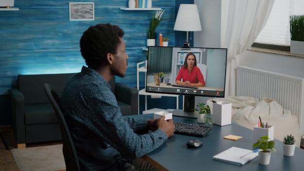 Inzoomen op zwarte man die op afstand werkt en met baas praat via online webcam terwijl hij thuis werkt...