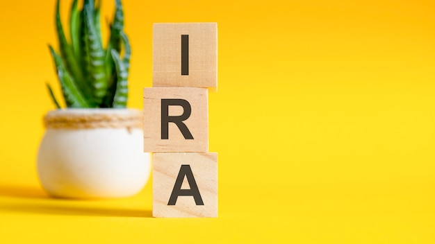 Ira concept met houten blokken op tafel, gele achtergrond
