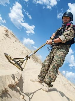Iraakse soldaat in de woestijn met legermetaaldetector
