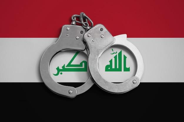 Irak vlag en politie handboeien. het concept van de naleving van de wet in het land en bescherming tegen criminaliteit