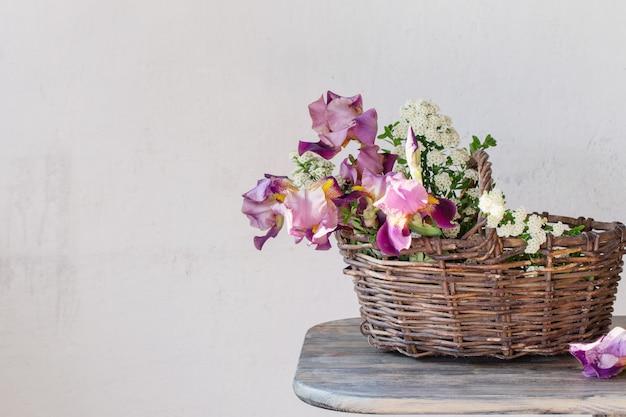 Irissen in mand op houten tafel tegen oppervlak van oude witte muur