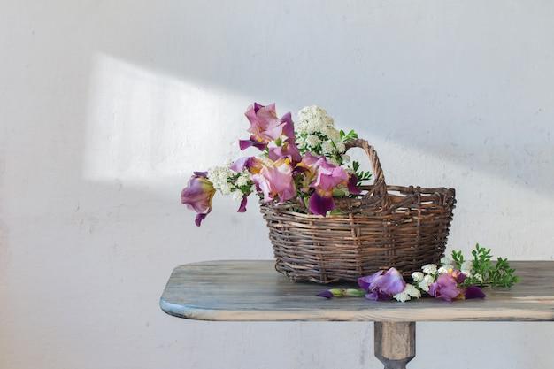 Irissen in mand op houten tafel tegen oude witte muur