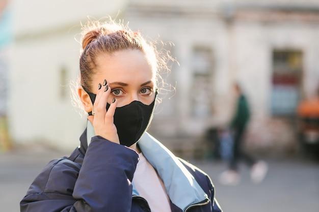 Irl met beschermend masker over haar oog wrijven met vuile handen