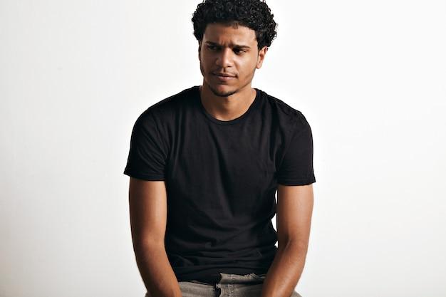 Ironische, doordachte knappe jongeman met een afro die een zwart mouwloos katoenen t-shirt op een witte muur draagt