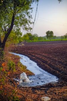 Irrigatiewaterstroom van pijp naar kanaal voor landbouwvelden, slow motion waterflits