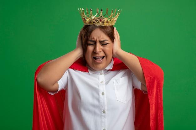 Irriterende superheld vrouw van middelbare leeftijd dragen kroon handen op oren geïsoleerd op groene achtergrond