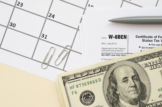Irs-formulier w-8ben certificaat van buitenlandse status van uiteindelijke begunstigde voor belastingheffing en rapportage van amerikaanse belasting voor blanco leugens met pen en honderd-dollarbiljetten op kalenderpagina