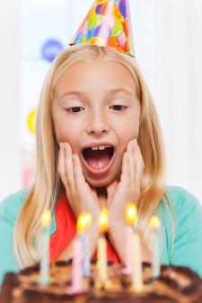 Is dat alles voor mij? gelukkig klein meisje dat naar de verjaardagstaart kijkt en er opgewonden uitziet