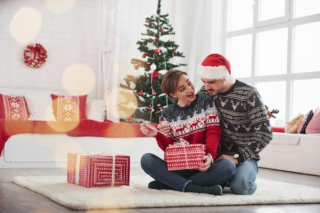 Is dat waar ik aan denk. man verrast zijn vrouw voor kerstmis in de mooie kamer met kerstversiering.