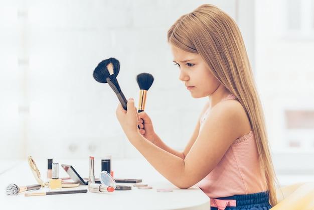 Is deze borstel voor contouren? zijaanzicht van peinzend klein meisje dat een van de twee make-upborstels kiest terwijl ze aan de kaptafel zit