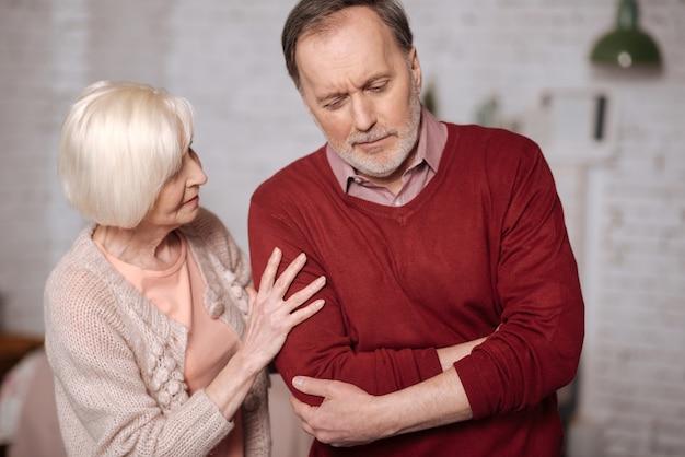 Is het een bijlage. portret van een oudere man die en zijn pijnlijke maagstreek raakt terwijl zijn liefhebbende vrouw hem steun geeft.