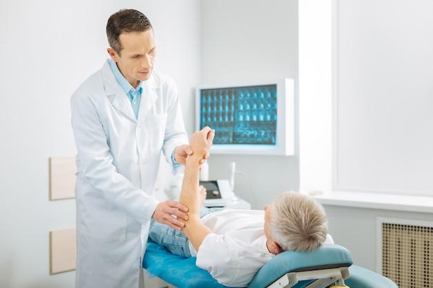 Is het pijnlijk. aardige knappe professionele arts die zich in de buurt van zijn patiënt bevindt en zijn arm opheft tijdens een medische controle