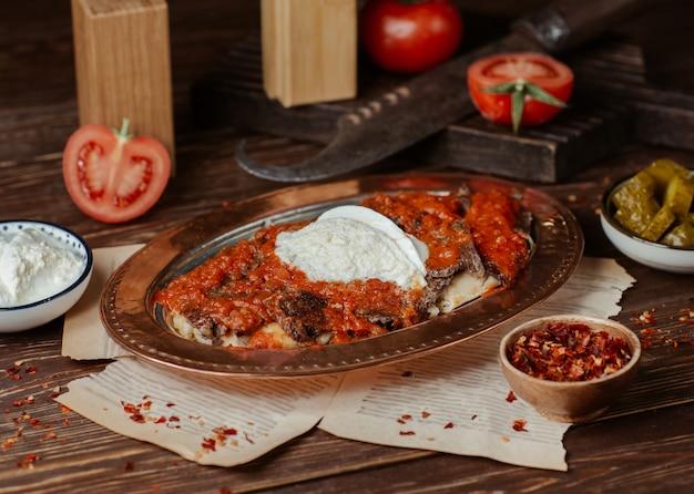 Iskender-kebab met tomatensaus en yoghurtroom