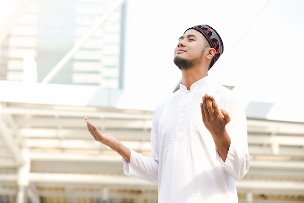 Islam moslim jonge mannen die openlucht op stadsachtergrond bidden