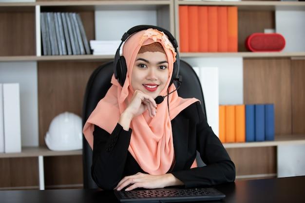 Islam zaken vrouw met hoofdtelefoon werken op kantoor.