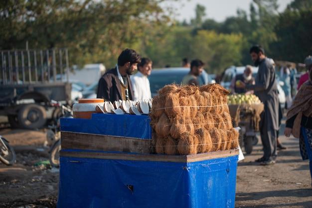 Islamabad, islamabad capital territory, pakistan - 03 februari 2020, een man verkoopt op straat gepelde kokosnoten en kokoswater.