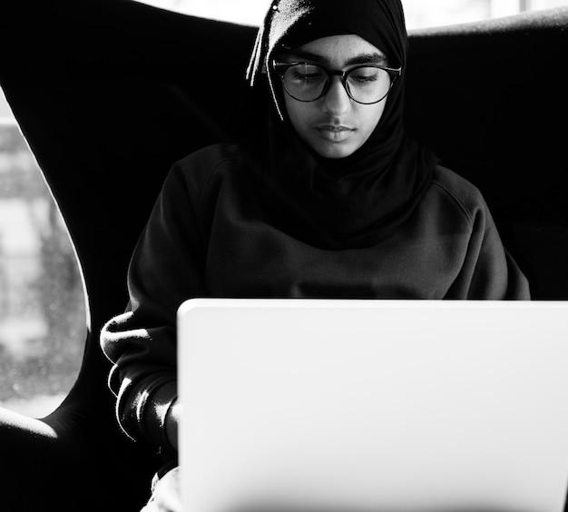 Islamitisch meisje dat met laptop bestudeert