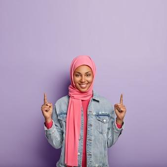 Islamitisch mode-concept. blij positieve vrouw met specifiek uiterlijk en kleding, wijst naar boven op vrije ruimte, laat iets naar boven zien, draagt modieuze jas. meisje in hijab maakt reclame voor object