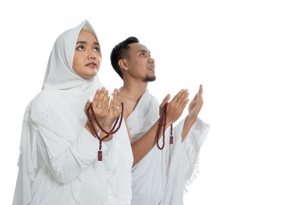 Islamitische man en vrouw bidden in witte traditionele kleding ihram
