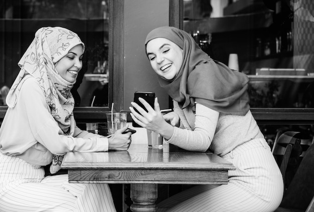 Islamitische vrienden praten en kijken op de slimme telefoon