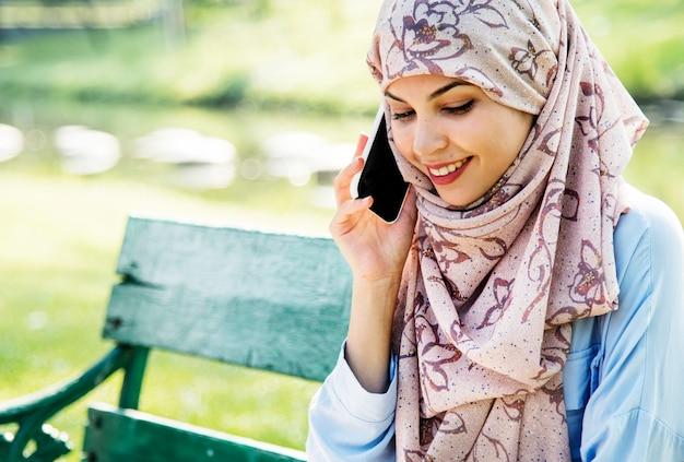Islamitische vrouw die mobiele telefoon met het glimlachen bij park met behulp van