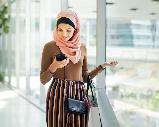 Islamitische vrouw die op de telefoon kijkt