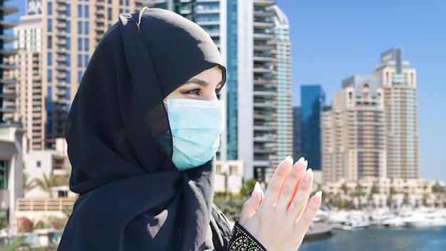 Islamitische vrouw in masker bidt tot god op de achtergrond van de stad.