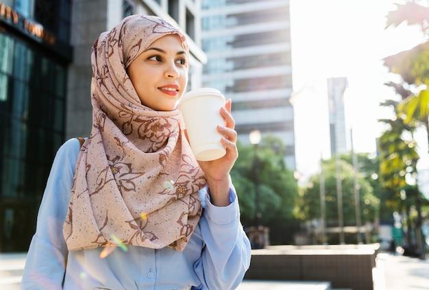 Islamitische vrouw koffie drinken in de stad