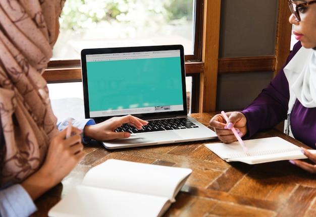 Islamitische vrouwen die laptop bespreken en gebruiken voor het werken